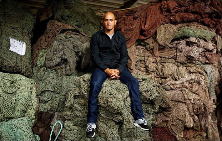 Kelly Slater sits with fishing nets collected for Outerknown