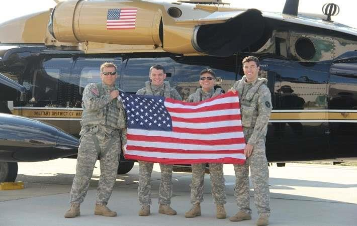 Sam Russo, founder of RePatriot Flag (far right), holding a RePatriot flag.
