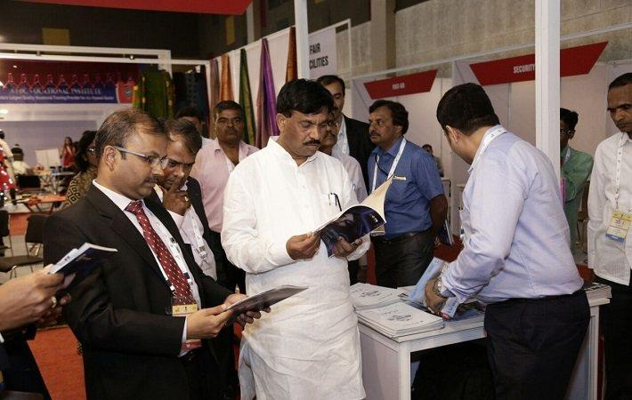 R Girish (extreme left) and Rudrappa Manappa Lamani (centre) reading Fibre2Fashion magazines at the Vastra fair.