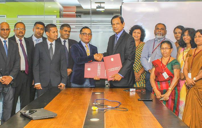 Brandix Chief People Officer Ishan Dantanarayana (centre, on left) and VTA Chairman/CEO Eng. Dr Lionel Pinto exchange the agreements in the presence of representatives of the two organisations.