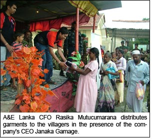 A&E Lanka CFO Rasika Mutucumarana distributes garments to the villagers in the presence of   the company