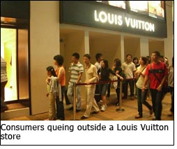 Consumers queing outside a Louis Vuitton store
